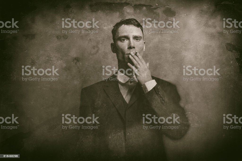 Antique wet plate photo of 1920s english gangster in suit smoking cigarette. stock photo