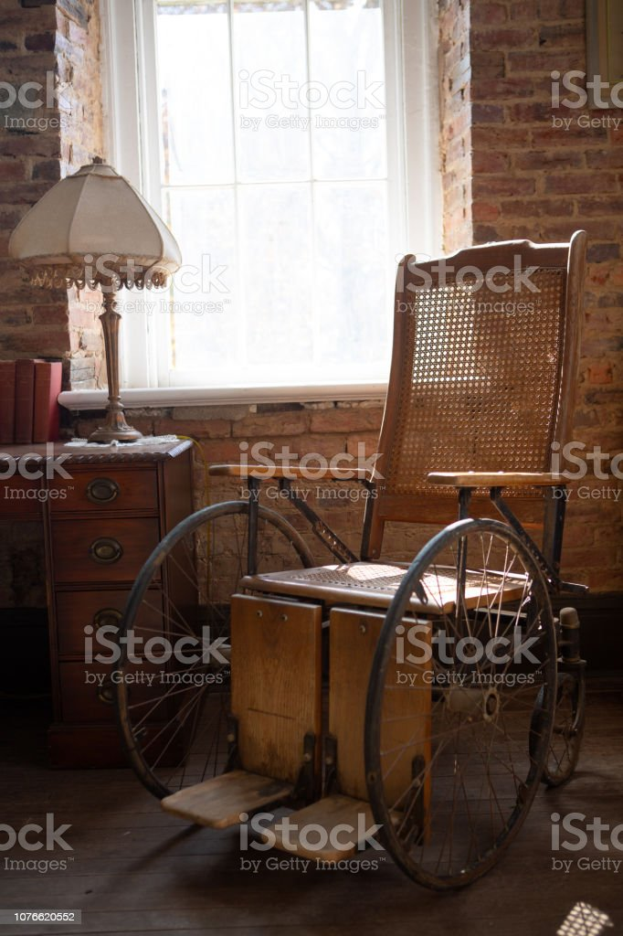 Antique wheelchair in a sunlit room stock photo