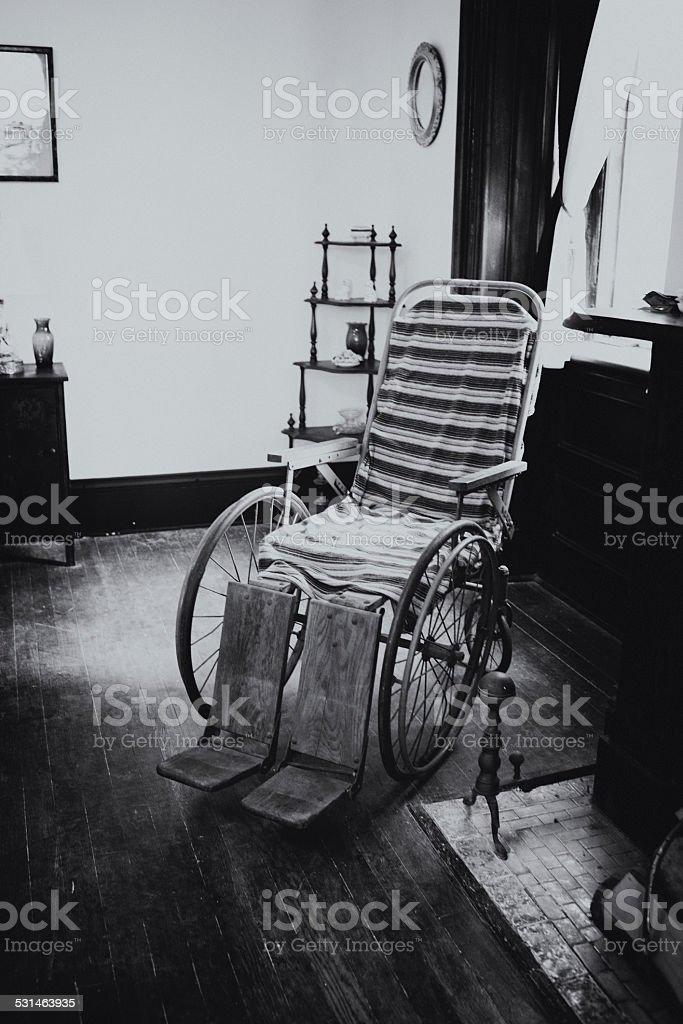 Antique Wheelchair in abandoned hospital Sitting Room stock photo