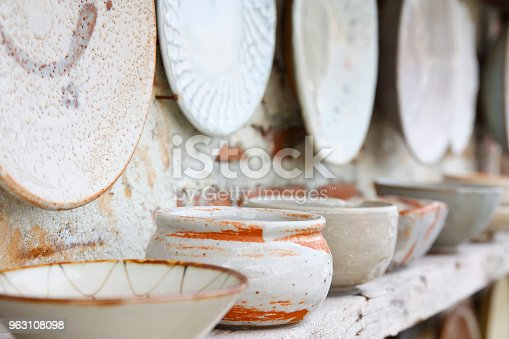 istock antique white and color cup jar dish and bowl vintage and retro on the old wood shelf and white brick wall for interior or exterior architecture decor background 963108098