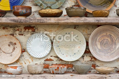 istock antique white and color cup jar dish and bowl vintage and retro on the old wood shelf and white brick wall for interior or exterior architecture decor background 963108140