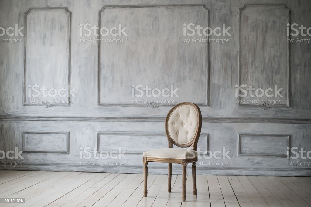 Antique white chair over luxury light wall design bas-relief stucco mouldings roccoco elements royalty-free stock photo