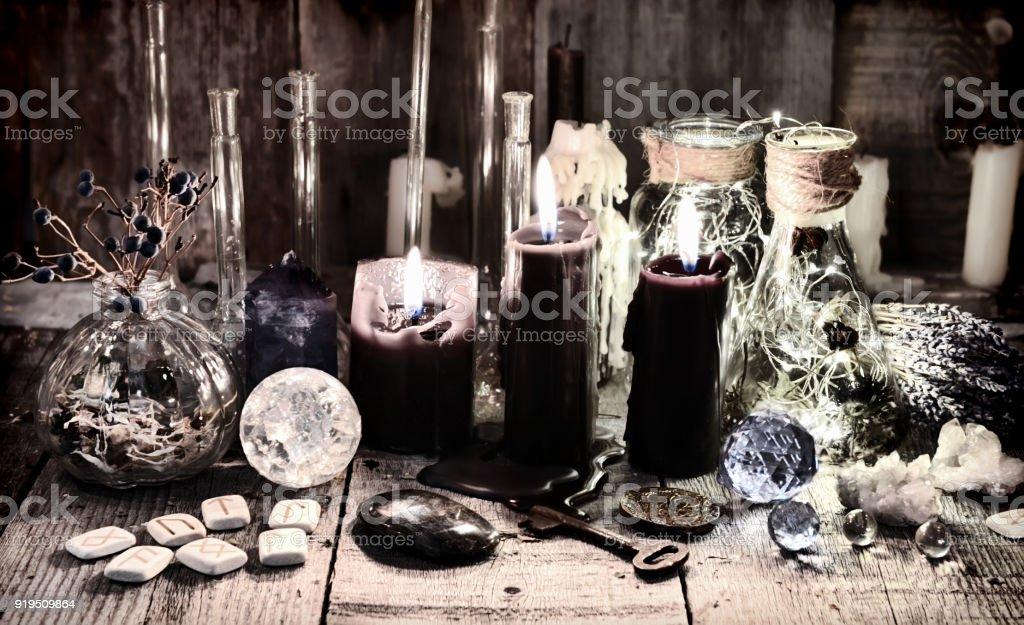 Antique witch book with lavender flowers, magic ritual objects, healing herbs, crystal and black candles stock photo