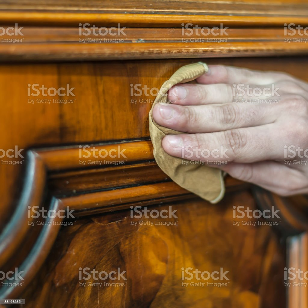 Hand applying oil and wax on a old wood furniture