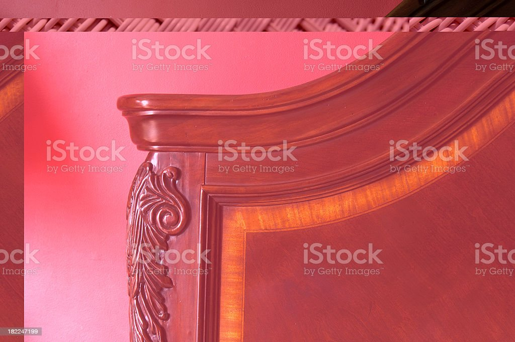 Antique carved wood headboard with a red wall in the background.