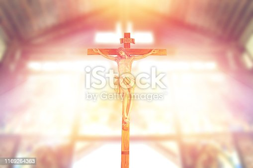 antique wooden crucifix, jesus on the cross in church with ray of light from stained glass, image of the crucifixion