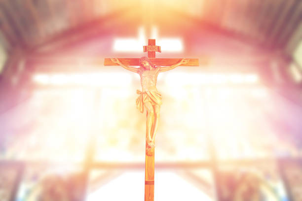 antique wooden crucifix, jesus on the cross in church with ray of light from stained glass, image of the crucifixion stock photo