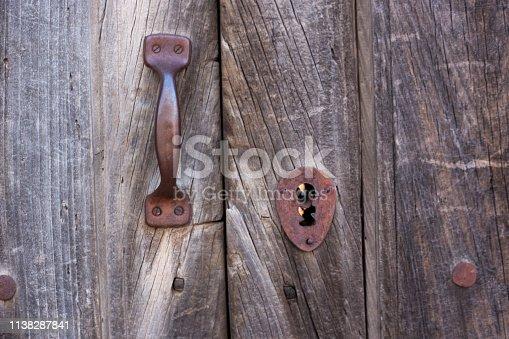 Antique Wooden Door Detail with Rusty Door Pull. Close-up shot.