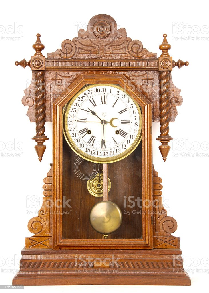 Antique wooden pendulum clock with Roman numerals stock photo