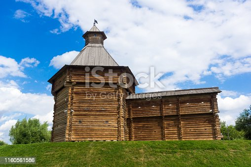Antique wooden tower with a fragment of a wall on a hill