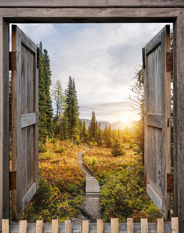 Antique wooden windows open to autumn wilderness at sunrise in national park