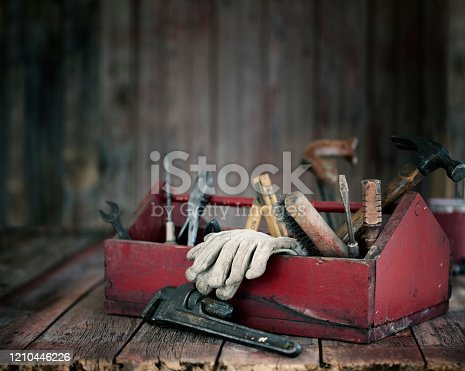 Antique work tools in a red toolbox on an old wood background