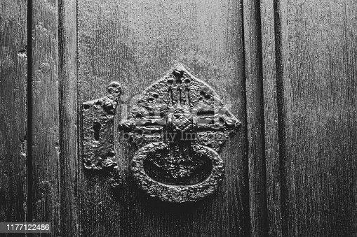 Close up of an antique wrought iron door handle on the wooden door of a church.  Belfast, Northern Ireland.