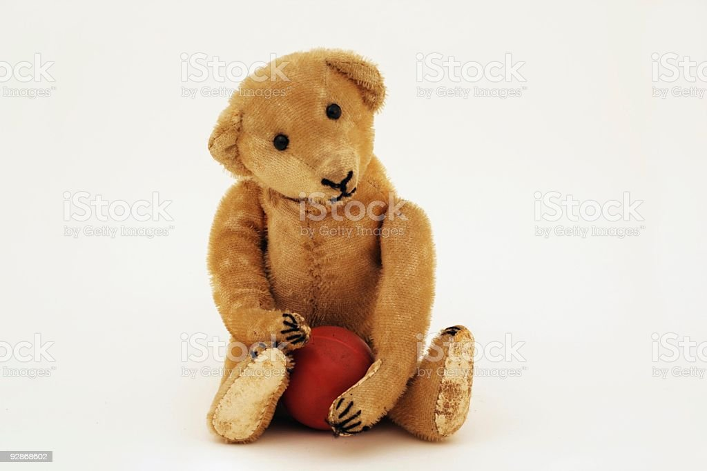 Antique  yellow teddy bear sitting and holding   a red ball. royalty-free stock photo