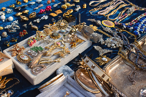 Antiques on flea market or seasonal festival - vintage jewelry, silver brooches and other vintage things. Collectibles memorabilia and garage sale concept, selective focus