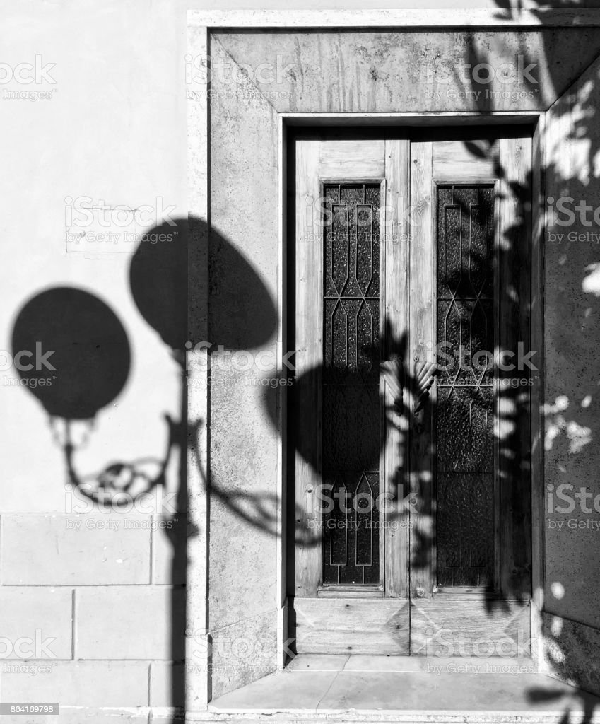 Antique-style street lamp casts shadow on elegant front door royalty-free stock photo
