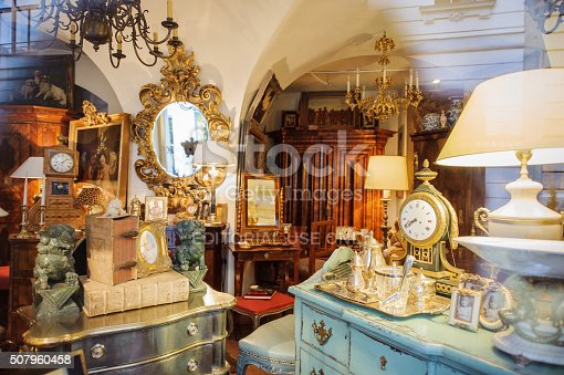 Vienna, Austria - July 4, 2011: Antiquities shop window shopping seen from the street - Kohlmarkt street in Vienna. The vintage store sells old clocks, old mirrors, old table sets, old furniture, vintage objects, vintage lamps, vintage books and other hobby items