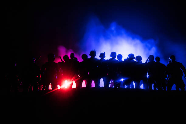 Anti-riot police give signal to be ready. Government power concept. Police in action. Smoke on a dark background with lights. Blue red flashing sirens. – zdjęcie