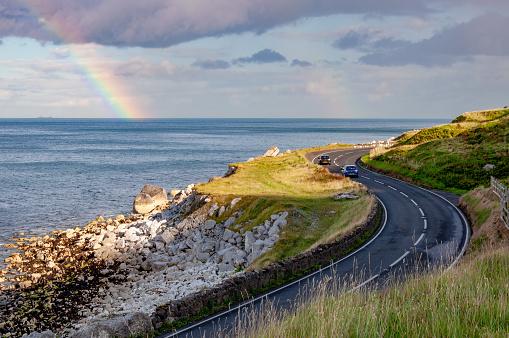 Antrim Coastal Road and rainbow in Northern Ireland, UK
