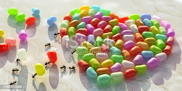 A conceptual image of ants working together in harmony arranging jelly beans in the shape of a heart on a marble counter / worktop. Three ants are carrying the last beans to complete the shape as other ants move around.