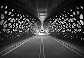 Symmetry in black and white of a pedestrian and cycling bridge in the city center of Antwerp, Belgium.