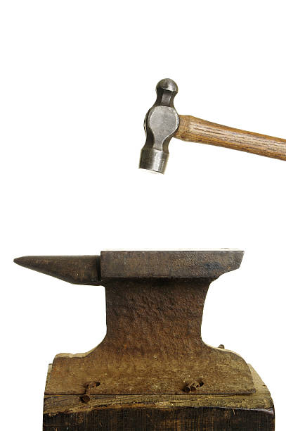 Anvil and Hammer A small anvil being hit by a hammer. anvil stock pictures, royalty-free photos & images
