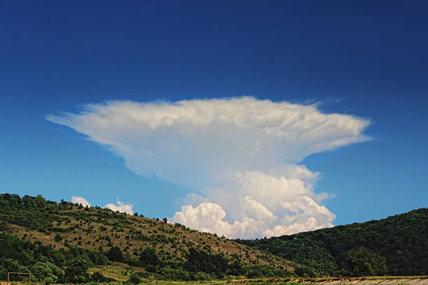 Anvil Storm Cloud and Blue Sky with Hills Anvil Storm Cloud and Blue Sky with Hills anvil stock pictures, royalty-free photos & images