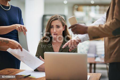 Shot of a young businesswoman looking anxious in a demanding office environment