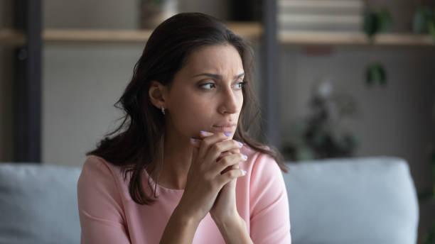 Anxious Arabic woman feel unhappy thinking at home stock photo