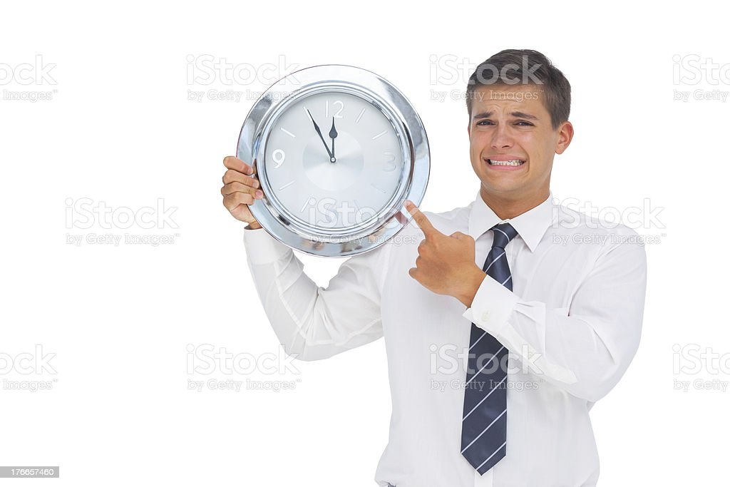 Anxious businessman holding and showing a clock royalty-free stock photo