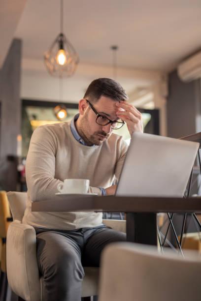 Anxious businessman working on laptop computer stock photo