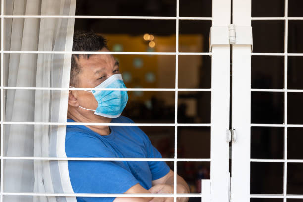 Ängstlicher chinesischer Mann mit Gesichtsmaske selbst isolieren Quarantäne zu Hause aus Angst vor Kontakt covid-19 Virus – Foto