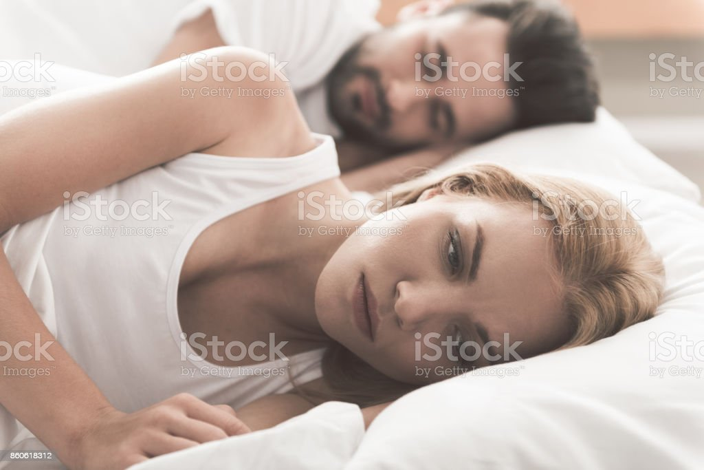 Anxious girl cannot sleep near her husband in bedroom stock photo