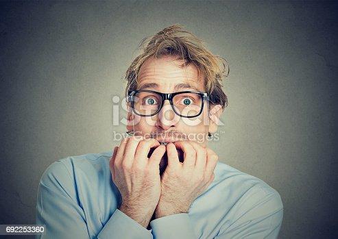 istock anxious man biting his fingernails craving for something 692253360