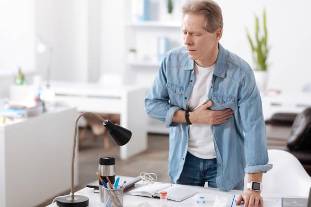 Homem ansioso tendo ataque cardíaco - foto de acervo