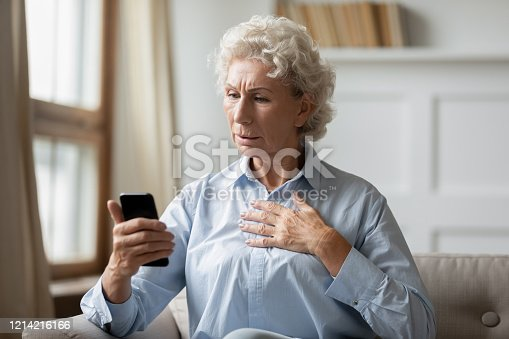 istock Anxious mature woman distressed by bad news on cellphone 1214216166