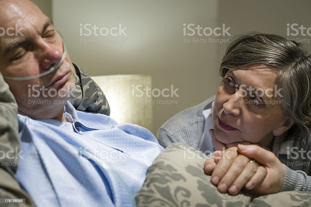Anxious old woman taking care of husband stock photo