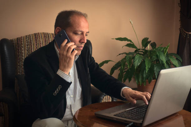 Anxious senior man phoning while working with his laptop at home stock photo