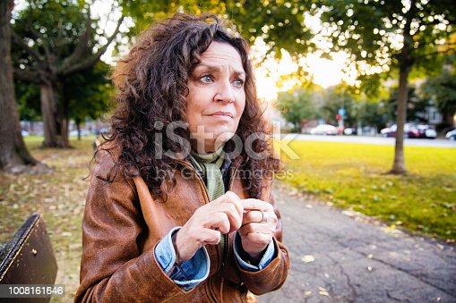 Anxious senior woman in crisis outdoors in park on an outdoors afternoon