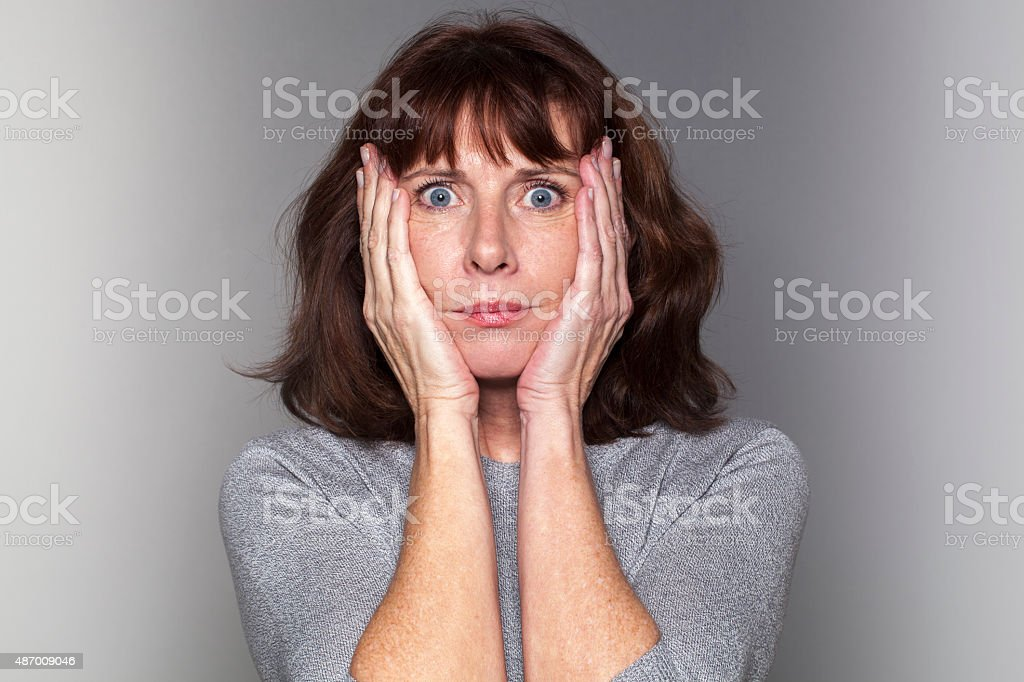 anxious senior woman under shock stock photo