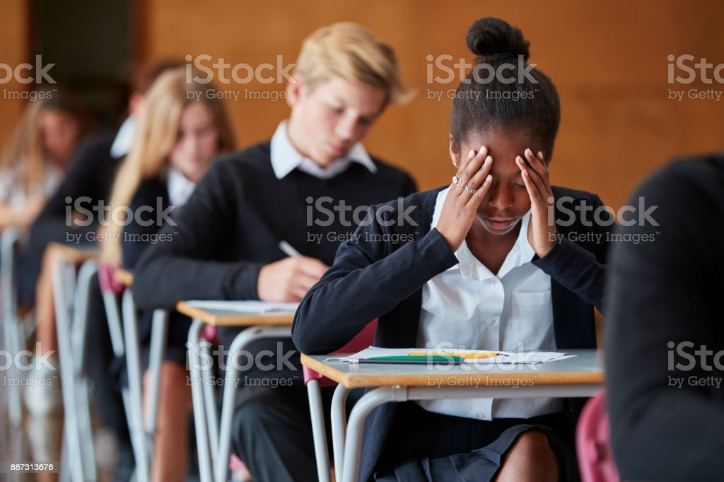 Anxious Teenage Student Sitting Examination In School Hall stock photo