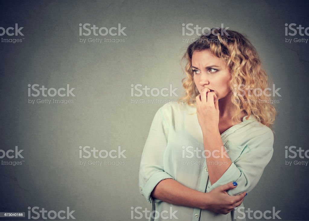 anxious woman biting her fingernails craving for something stock photo