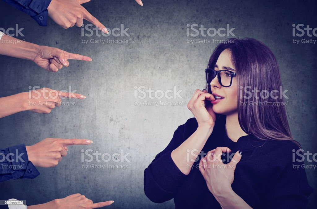 Anxious woman judged by different people stock photo