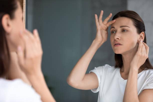 bezorgde vrouw die in spiegel kijkt, rakend voorhoofd, verward over rimpels - mirror mask stockfoto's en -beelden