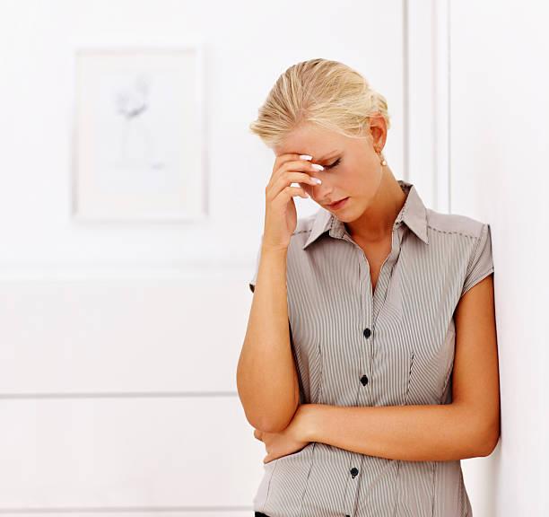 unruhig junge frau auf einer wand gelehnt - migräne vorbeugen stock-fotos und bilder