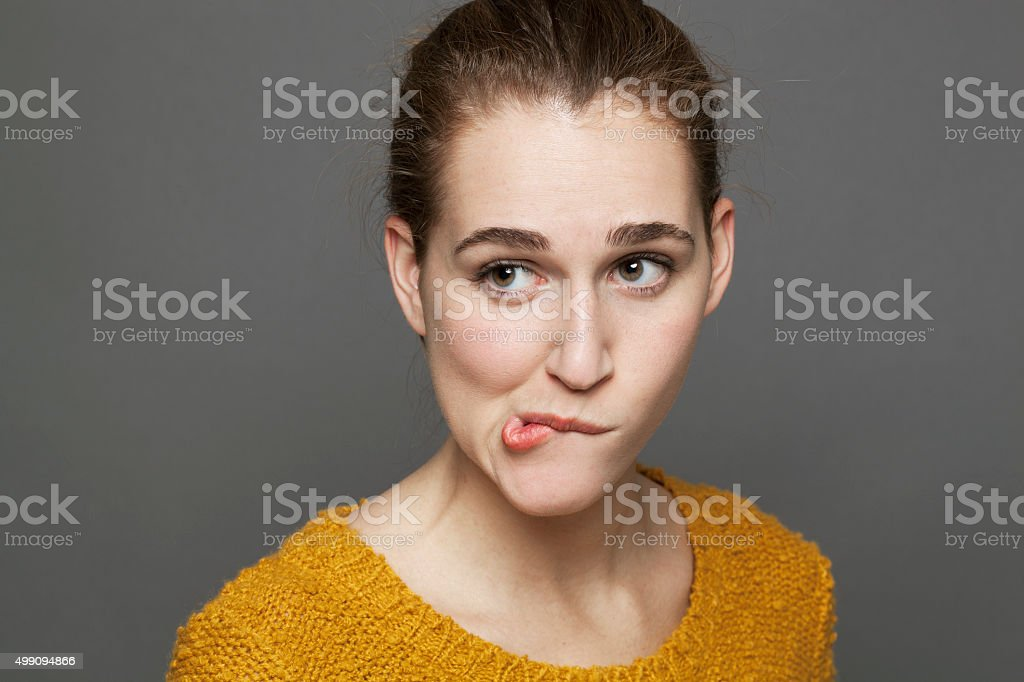 anxious young woman looking skeptical, biting her lips for confusion stock photo