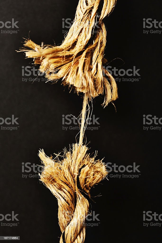 Any minute now. Breaking point! Frayed rope about to snap. stock photo