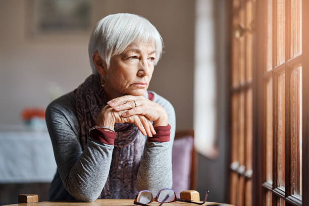 Any minute now... Shot of a senior woman looking thoughtful in a retirement home desolation stock pictures, royalty-free photos & images