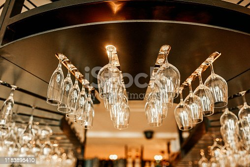 Cropped shot of wine glasses neatly arranged in a hanging wine rack in an empty bar