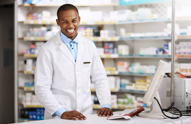 Anything I can assist with? Portrait of a young pharmacist working in a chemist pharmacist stock pictures, royalty-free photos & images